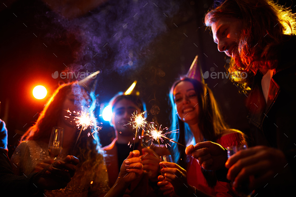 Friends lighting sparklers at birthday party - Stock Photo - Images