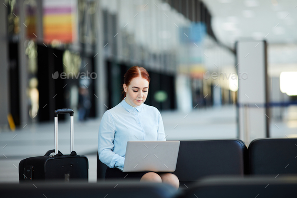 Businesswoman Using Laptop in Airport - Stock Photo - Images