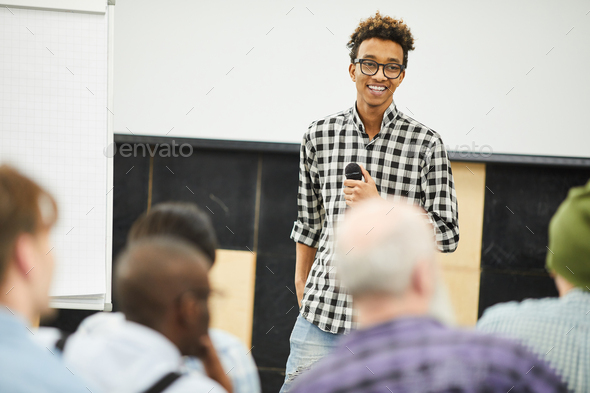 Positive successful young entrepreneur at business conference - Stock Photo - Images