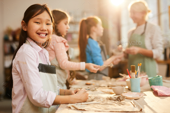 Smiling Asian Girl in Pottery Studio - Stock Photo - Images