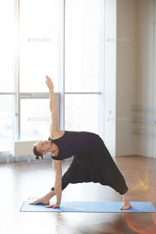 Performing extended triangle pose - Stock Photo - Images