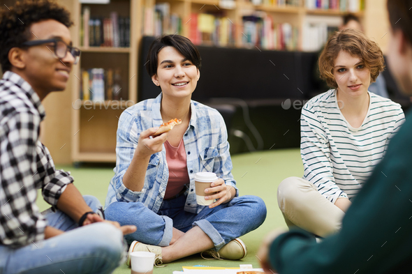 Positive students having lunch break in library - Stock Photo - Images