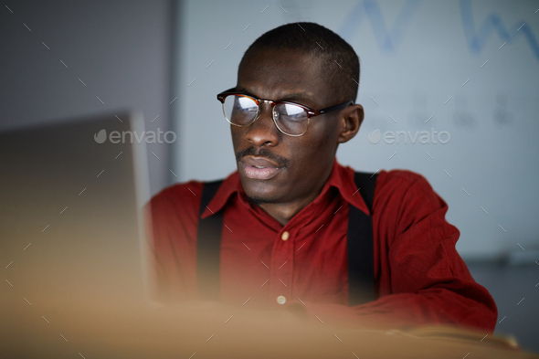 African Businessman Using Laptop in Dark Office - Stock Photo - Images