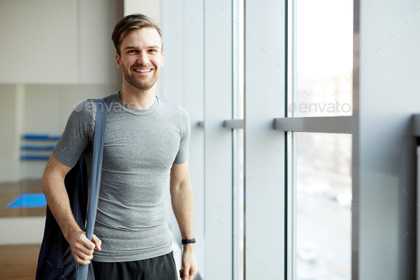 Cheerful man with yoga mat bag - Stock Photo - Images