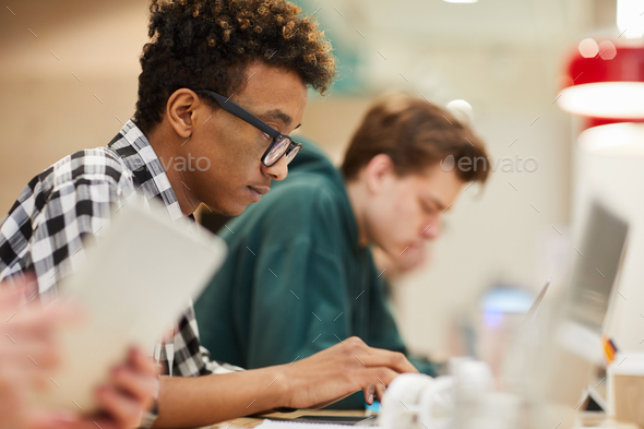 Black student concentrated on coding - Stock Photo - Images