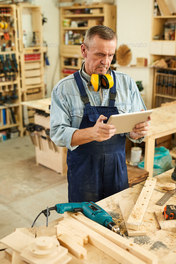 Senior Carpenter using Digital Tablet - Stock Photo - Images