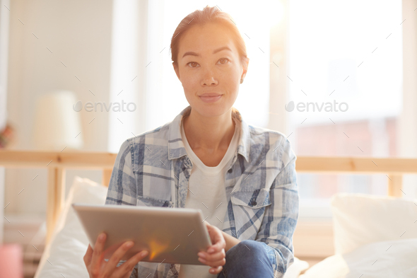 Asian Woman Using Tablet in Sunlight - Stock Photo - Images