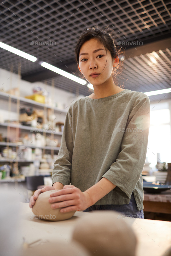 Asian girl working in pottery workshop - Stock Photo - Images