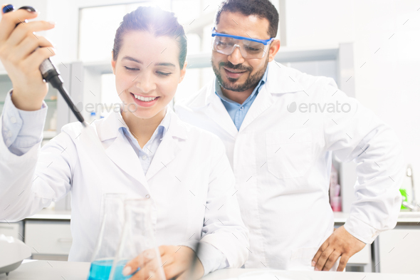 Chemists performing experiment in laboratory - Stock Photo - Images