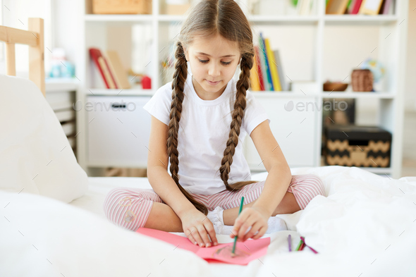Girl Drawing Pictures on Bed - Stock Photo - Images