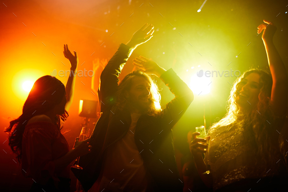 Positive youth dancing in smoky dark dance hall - Stock Photo - Images