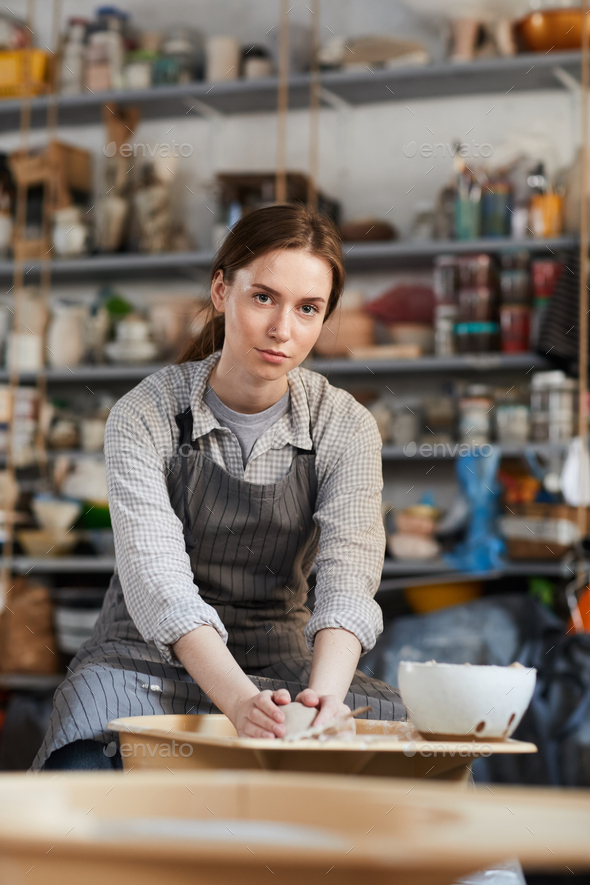 Woman forming vase on pottery wheel - Stock Photo - Images