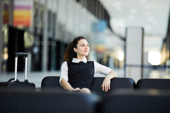 Smiling Woman Waiting in Airport - Stock Photo - Images