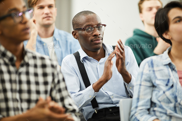 African conference participant applauding for speaker - Stock Photo - Images