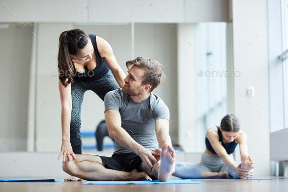 Yoga teacher adjusting pose of young man - Stock Photo - Images