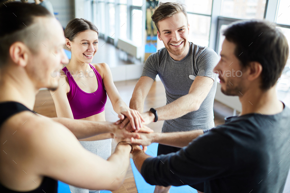 Fitness trainers stacking hands together - Stock Photo - Images