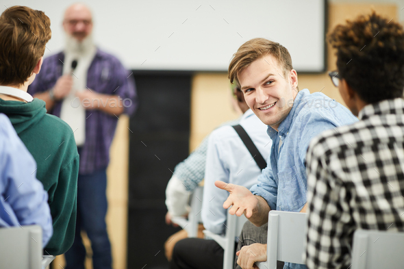 Students talking in auditorium during conference - Stock Photo - Images