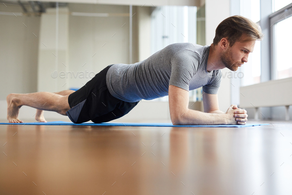 Concentrated man doing plank pose - Stock Photo - Images