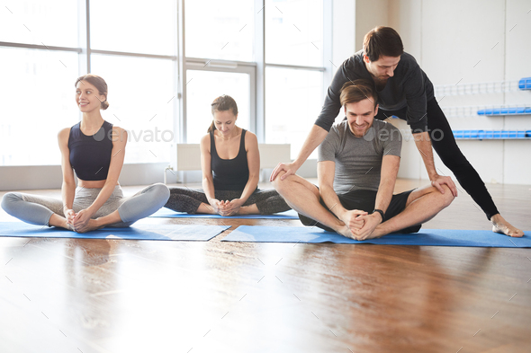 Assisting guy to stretch legs - Stock Photo - Images