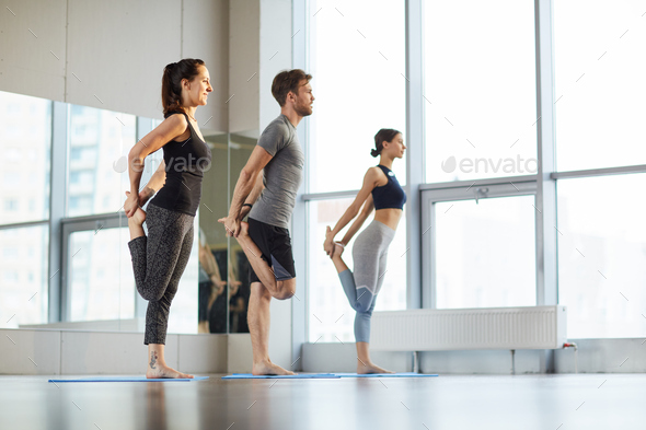 Stretching hips at yoga class - Stock Photo - Images