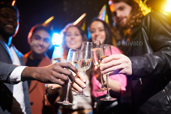 Full champagne flutes in hands of friends - Stock Photo - Images