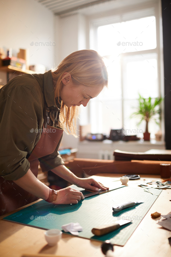 Female Artisan in Sunlit Shop - Stock Photo - Images