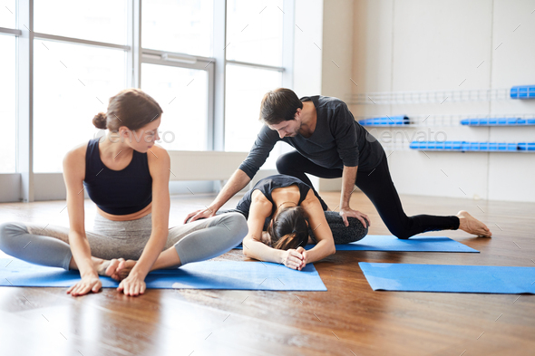 Yoga teacher correcting student at class - Stock Photo - Images