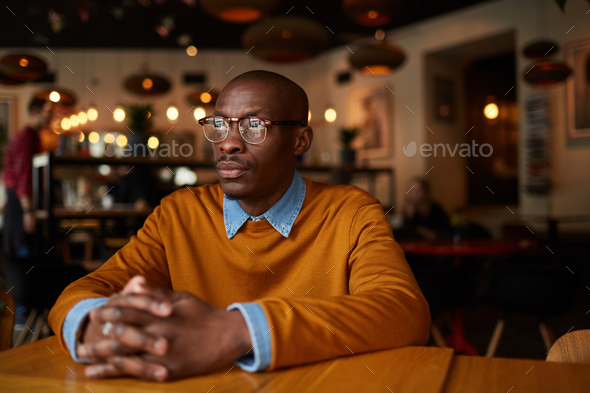Pensive African Man in cafe - Stock Photo - Images