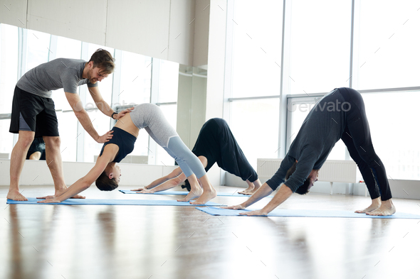 Qualified yoga coach assisting students at class - Stock Photo - Images