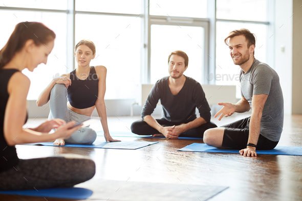 Talking to yoga teacher at class - Stock Photo - Images