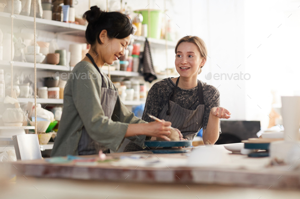 Young potters chatting while working in ceramic studio - Stock Photo - Images