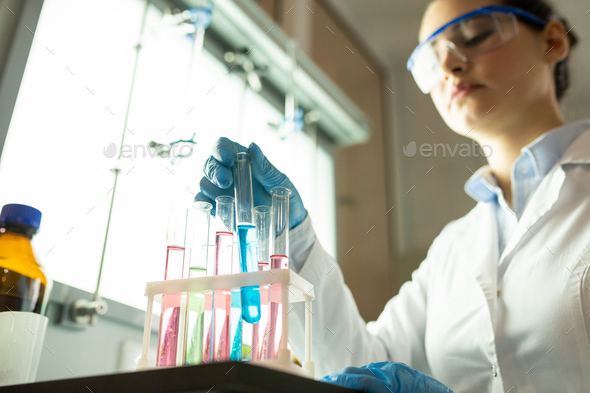 Laboratory worker sorting test tubes with colorful liquids - Stock Photo - Images
