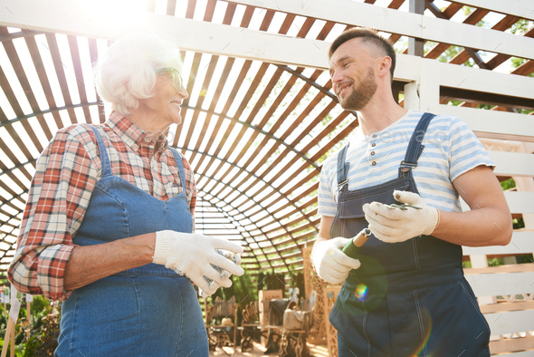 Two Smiling Gardeners in Sunlight - Stock Photo - Images