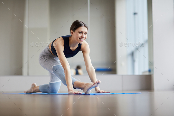 Cheerful woman stretching leg - Stock Photo - Images