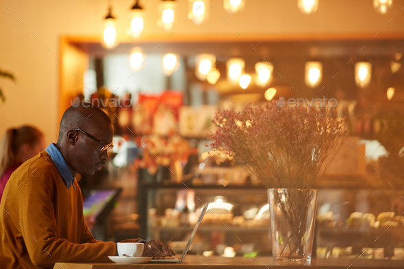 Contemporary African Man Working in Cafe - Stock Photo - Images