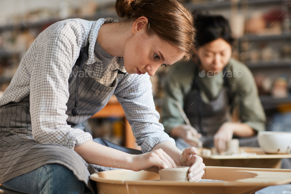 Serious woman making pot in workshop - Stock Photo - Images