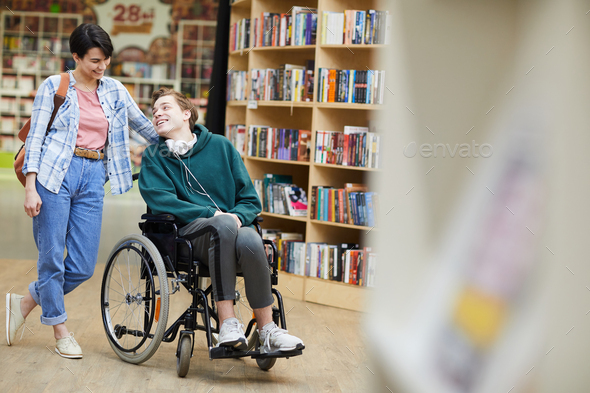 Disabled student visiting library with groupmate - Stock Photo - Images