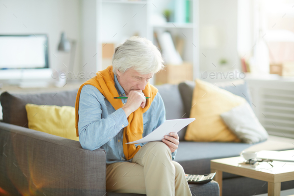 Frowning Senior Man Looking at Document - Stock Photo - Images