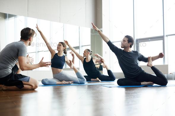 Yoga coach explaining how to do one-legged king pigeon pose - Stock Photo - Images