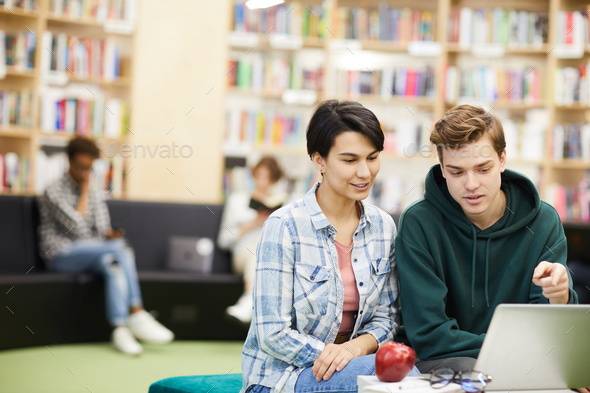 Discussing university project in library - Stock Photo - Images