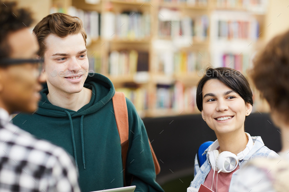 Positive students chatting in library - Stock Photo - Images