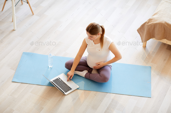 Pregnant Woman Watching Workout Videos - Stock Photo - Images
