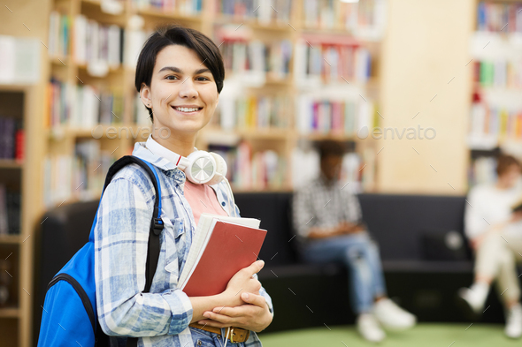 Confident university student in library - Stock Photo - Images