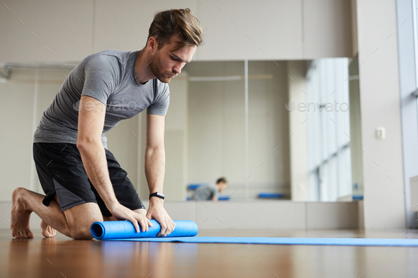 Young man packing yoga mat - Stock Photo - Images