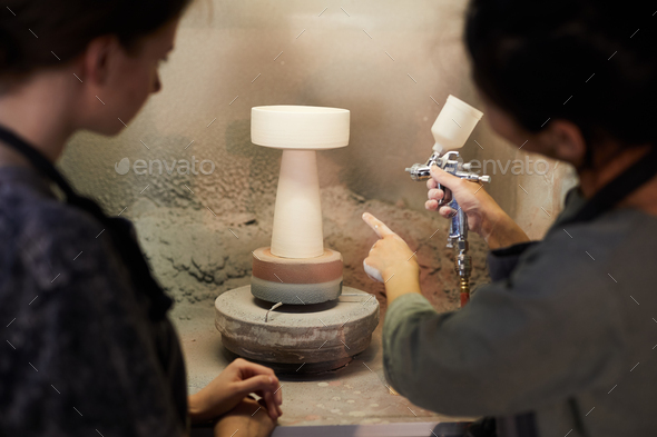 Using paint sprayer in workshop - Stock Photo - Images