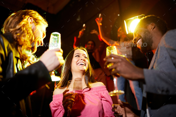 Excited lady between two guys at party - Stock Photo - Images