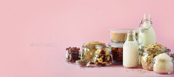 Glass bottles of vegan plant milk and almonds, nuts, coconut, hemp seed milk on pink background - Stock Photo - Images
