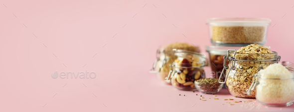 Vegan health food over pink background with copy space. Nuts, seeds, cereals, grains in glass jars - Stock Photo - Images