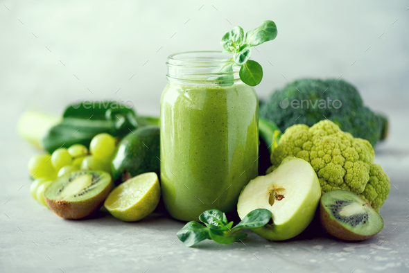 Glass jar mugs with green health smoothie, kale leaves, lime, apple, kiwi, grapes, banana, avocado - Stock Photo - Images