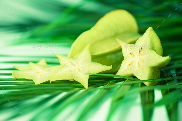 Exotic star fruit or averrhoa carambola over tropical green palm leaves on turquoise background - Stock Photo - Images